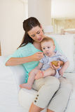 Happy mother eating with her baby boy Stock Photography