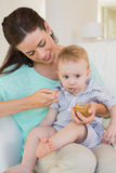 Happy mother eating with her baby boy Stock Images