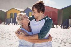 Happy mother embracing her son at beach. During sunny day stock photo