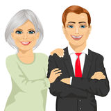 Happy mother embracing her son dressed in business suit standing with arms folded Royalty Free Stock Photography