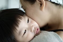 Happy mother embracing and kissing her son. Happy asian mother embracing and kissing her son royalty free stock photos