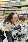Happy mother embracing and kissing her son in the store.  Stock Image