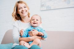 Happy mother embracing little child while sitting on couch. At home royalty free stock images