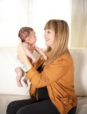 Happy mother enjoying her time with her newborn baby boy. Happy mother enjoying a special moment with her newborn baby boy on a white sofa in a white living Stock Image