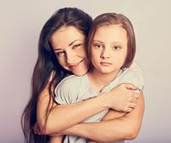 Happy mother and excited joying kid girl hugging with emotional smiling faces on purple background with empty copy space stock images