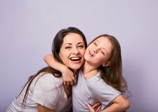 Happy mother and excited joying kid girl hugging with emotional smiling faces on purple background with empty copy space royalty free stock image