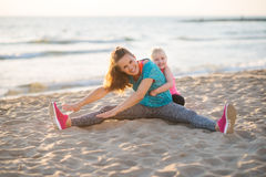 Happy mother exercising with daughter on the beach at sunset Royalty Free Stock Photos