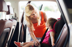 Happy mother fastening child with car seat belt Royalty Free Stock Photography