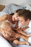 Happy mother father and baby laughing together Stock Image