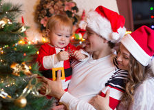 Happy mother and father with baby near Christmas tree Stock Photography