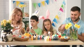 Happy mother, father and children having fun while painting and decorating eggs for holiday stock video