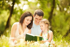 Happy mother, father and daughter in the park stock images