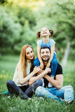 Happy mother, father and daughter in the park. Beauty nature scene with family outdoor lifestyle. Happy daughter on father back sm. Happy mother, father and Stock Photos