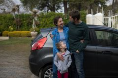 Father, mother and daughter standing near the car stock photography