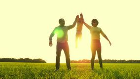 Happy mother and father holding a child`s hands raise it, against the background of sunset. The concept of a happy stock footage
