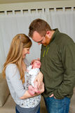 Happy Mother and Father Holding Newborn. A newborn baby boy is being held in the arms of his happy dad and mom a short while after birth Stock Image