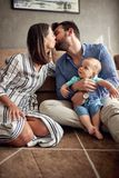 Happy mother and father holding their baby boy and kissing at ho stock photography
