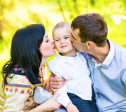 Happy mother and father kissing his little son  in park Royalty Free Stock Photo