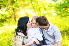 Happy mother and father kissing his little son  in park Royalty Free Stock Images