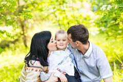 Happy mother and father kissing his little son  in park Stock Photo