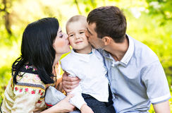 Happy mother and father kissing his little son in park Stock Images