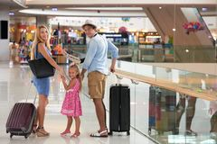 Traveling family. Happy mother, father and little daughter with suitcases ready for traveling royalty free stock photos