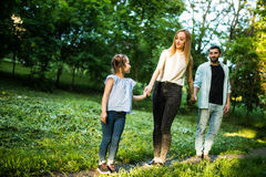 Happy mother, father and little girl walking in summer park and having fun Royalty Free Stock Photography