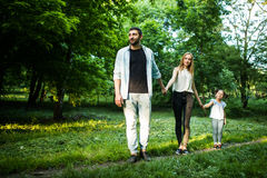 Happy mother, father and little girl walking in summer park and having fun Stock Image
