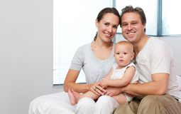 Happy mother and father sitting at home with cute baby Stock Images