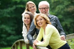Happy mother and father standing with two daughters outdoors Stock Photos