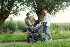 Happy mother and father walking outdoors with baby in pram Stock Images