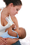 Happy Mother Feeding Baby Boy with Milk Bottle Royalty Free Stock Photo