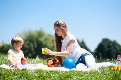 Happy mother feeding baby boyl. Outdoors Royalty Free Stock Images