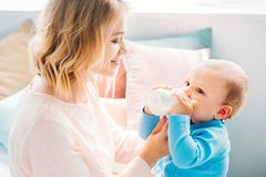 Happy mother feeding her little child. With baby bottle at home royalty free stock image