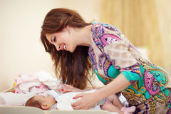 Happy mother feeding infant baby from bottle Royalty Free Stock Image