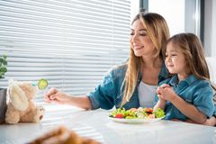 Happy mother feeding little girl playfully Royalty Free Stock Photos