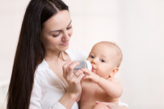 Happy mother feeds her baby bottle Royalty Free Stock Photo