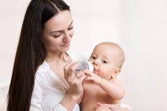 Happy mother feeds her baby bottle. Happy mother feeds her baby from bottle Royalty Free Stock Photo