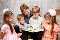 Happy mother and four children reading a book. Royalty Free Stock Image