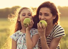 Happy mother and fun enjoying kid girl have a picnic and eating Stock Photography