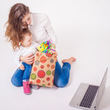 Happy mother and funny baby taking purchases Royalty Free Stock Images