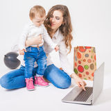 Happy mother and funny baby taking purchases Royalty Free Stock Photo