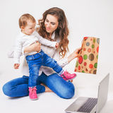 Happy mother and funny baby taking purchases Stock Photography