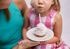 Happy mother and girl blowing out cupcake candle Royalty Free Stock Photos