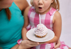 Happy mother and girl blowing out cupcake candle Stock Image