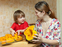 Happy mother with girl cooks pumpkin Stock Photos