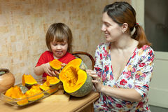 Happy mother with girl cooks pumpkin Royalty Free Stock Photography