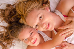 Happy mother and girl laying in bed Stock Photo