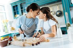 Happy mother and girl making some delicious cookies. I love you. Pretty inspired dark-haired daughter and her mother smiling and embracing while making some Royalty Free Stock Photography