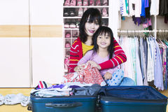Happy mother and girl prepare clothes. Portrait of happy mother her daughter smiling at the camera while preparing their clothes for holiday Royalty Free Stock Photo